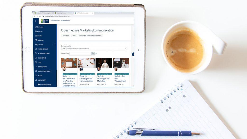 Symbolbild eines Studententisches mit Ipad auf dem der Online-Campus geöffnet dargestellt wird